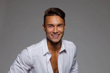Photo pour Bel homme en chemise déboutonnée blanche de sourire. Portrait en studio sur fond gris. - image libre de droit