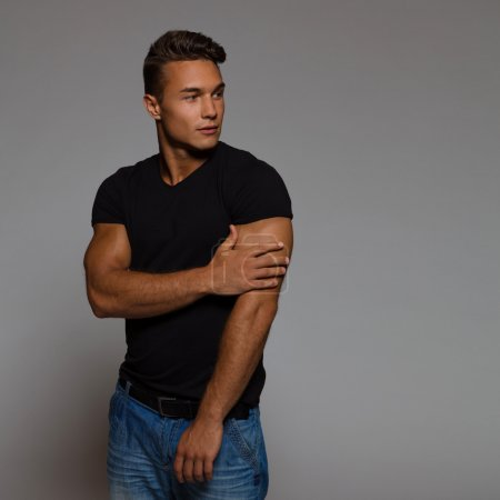 Photo for Handsome man in black t-shirt looking away. Waist up studio shot on gray background. - Royalty Free Image