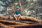 Backpacker man sitting on wood trunk