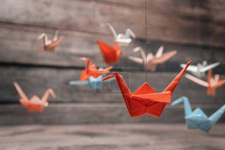 Foto de Grullas de papel origami muchas coloridas sobre fondo de madera - Imagen libre de derechos