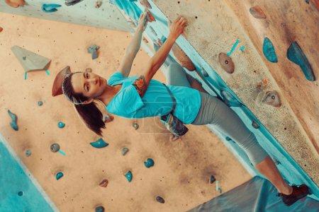 Beautiful girl climbing in gym