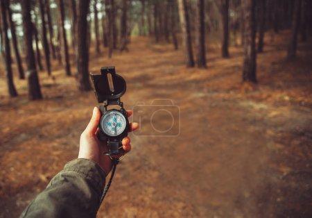 Photo pour Femme randonneuse cherchant direction avec boussole dans la forêt. Vue des mains. Prise de vue. Espace pour le texte à droite à gauche de l'image - image libre de droit