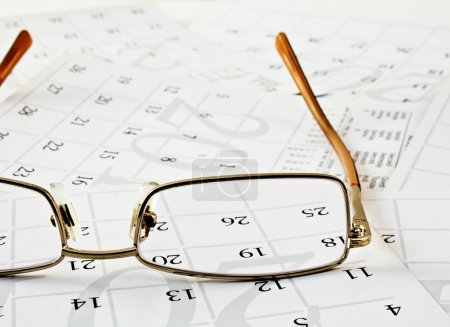 Glasses on calendar pages