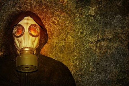 Photo pour Homme masqué à la lumière des flammes sur un fond de mur en béton - image libre de droit