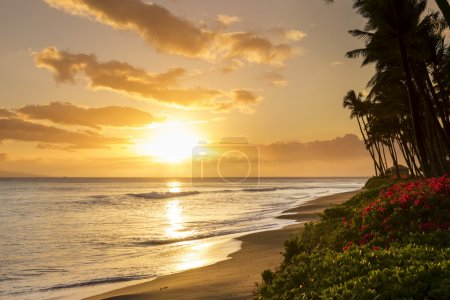 Beautiful, warm tropical sunset on the white sands of Kaanapali Beach in Maui, Hawaii. A fabulous destination for vacation and travel.