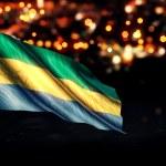 Постер, плакат: Gabon National Flag City Light Night Bokeh Background 3D