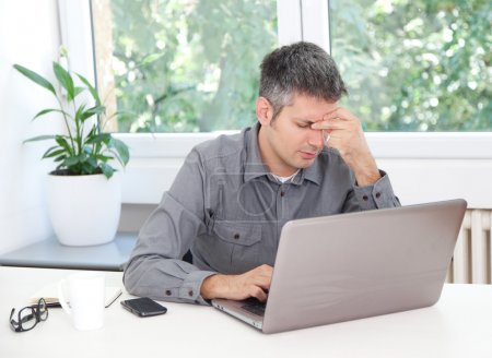 Photo for Image of a man at the desk, having headache - Royalty Free Image