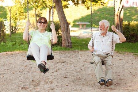 Foto de Senior pareja divirtiéndose en el parque de columpios - Imagen libre de derechos