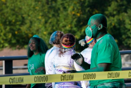 Green worker in a color run race with mask