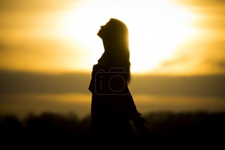 Photo for The sun stands at the horizon and the girl becomes a very nice black silhouette. - Royalty Free Image