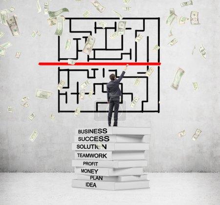 Homme debout sur une pile de livres avec des mots clés d'affaires écrits sur le dos et la peinture ligne rouge, dollars tombant d'en haut .