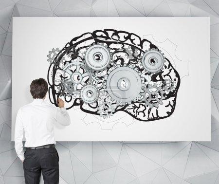 Photo pour Homme d'affaires dessin image du cerveau avec des engrenages sur affiche blanche. Vue de derrière. Fond gris. Concept de travail mental . - image libre de droit