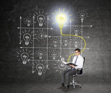 Photo pour Un homme d'affaires assis sur une chaise roulante et lisant un livre, un système d'ampoules dessinées derrière lui, le livre et l'ampoule jaune brillant liés. Fond noir. Concept d'étude - image libre de droit