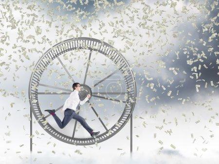 Photo pour Jeune homme d'affaires au volant d'une roue, dollars tombant d'en haut. Ciel gris à l'arrière-plan. La notion de dur labeur. - image libre de droit
