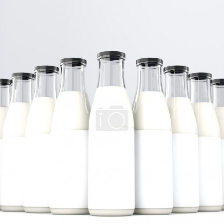 Glass bottles of milk with black lid arranged in pyramid. Front view. Concept of producing milk.