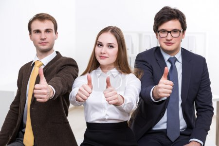 Two businessmen with woman in between, their thumbs up. Office. Concept of team work.