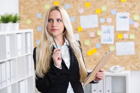 Businesswoman with pencil at her chin and notepad. Office at background.