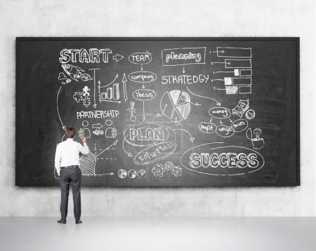 Businessman drawing business scheme on blackboard, concrete background.