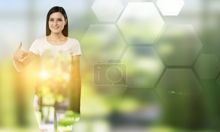 Young woman pointing at blank hexagonals to the right.