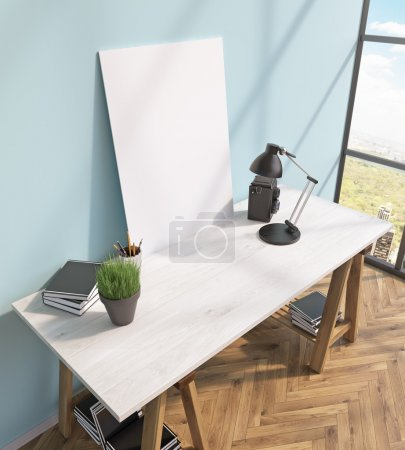 Blank frame on white table, books on and under table, lamp, window to the right.