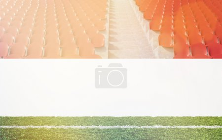 Blank banner around pitch, red seats, aisle between them. Front view.