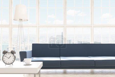 Sofa at panoramic window, coffee table with alarm clock beside.