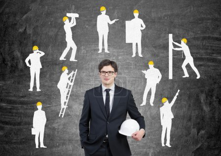 Businessman with white helmet, silhouettes of businessmen with different construction tasks around him, Black background. Concept of business construction.
