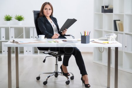 Businesswoman in suit with notebook sitting at table, tablet and coffee on it. Concept of work.