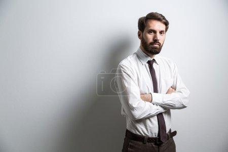 Photo pour Homme d'affaires en chemise blanche debout contre un mur blanc avec les bras croisés. Maquette - image libre de droit
