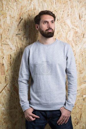 Photo pour Homme barbu en sweat-shirt gris sur fond brun clair texturé. Maquette - image libre de droit