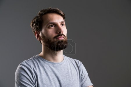 Photo for Portrait of bearded man in grey shirt looking away from the camera on dark grey background - Royalty Free Image