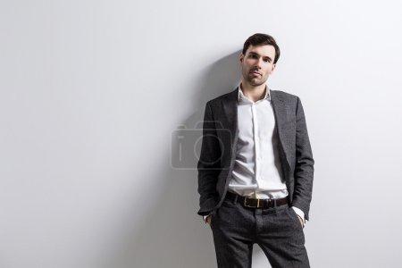 Photo pour Homme d'affaires avec les mains dans des poches isolées sur un mur blanc. Maquette - image libre de droit