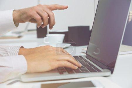 Photo pour Sideview de deux hommes d'affaires à l'aide d'ordinateur portable au bureau - image libre de droit
