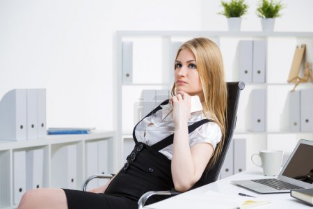 Photo for Thoughtful businesswoman with hand at chin sitting on chair at office desk - Royalty Free Image