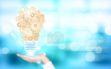 Photo for Idea concept with businesswoman hand holding abstract lightbulb made of golden gears on blue background - Royalty Free Image