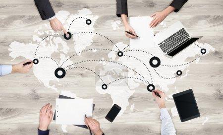 Photo pour Concept de réseautage mondial avec une équipe d'hommes d'affaires travaillant sur une surface en bois avec carte, réseau et appareils électroniques - image libre de droit