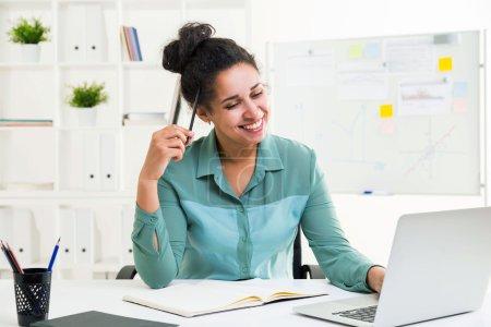 Photo pour Heureuse femme afro-américaine souriante utilisant un ordinateur portable sur le bureau avec un bloc-notes et d'autres articles de papeterie - image libre de droit