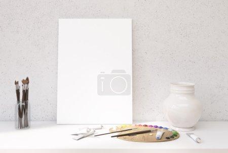 Photo pour Vue de face du bureau blanc avec toile vierge appuyée sur le mur en béton, palette de peinture à l'huile et tubes, vase décoratif et ensemble de pinceaux. Maquette, rendu 3D - image libre de droit