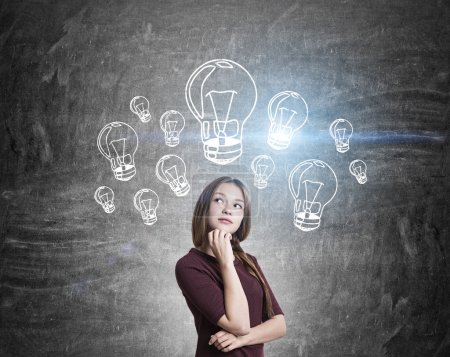Photo pour Idea concept with thoughtful girl and illuminated light bulb sketches on chalkboard background - image libre de droit