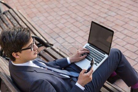 Photo pour Vue latérale du jeune homme d'affaires assis sur un banc extérieur et utilisant un ordinateur portable avec écran vierge et téléphone intelligent. Maquette - image libre de droit