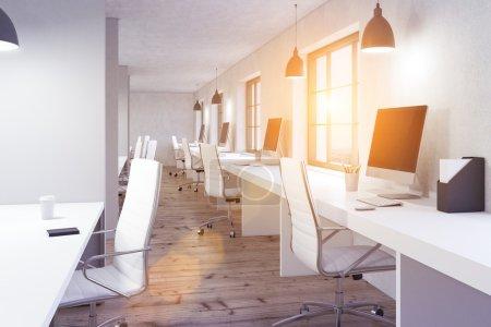 Photo pour Intérieur de bureau de coworking avec plancher en bois, bureaux blancs, écrans d'ordinateur vierges et fenêtre avec vue sur la ville et ensoleillement. Image tonique, rendu 3D - image libre de droit