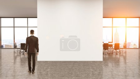 Businessman in suit against blank wall