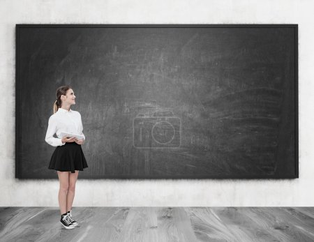Photo for Young woman standing near blackboard holding tablet. Concept of studying at modern establishment. Mock up - Royalty Free Image