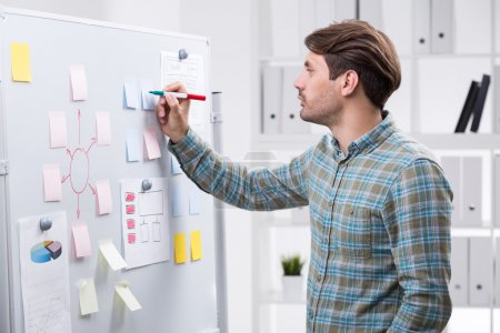 Foto de Hombre de negocios tomando notas en etiqueta engomada de la pizarra. Estanterías con carpetas en segundo plano. Concepto de trabajo corporativo y planificación empresarial - Imagen libre de derechos