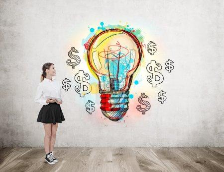 Foto de Mujer joven de pie cerca de la pared de hormigón con boceto de bombilla rodeada de signos de dólar. Concepto de nueva idea en marketing - Imagen libre de derechos