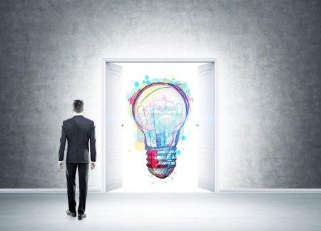 Photo pour Homme debout dans une pièce en béton avec double ouverture de porte pour révéler une grande esquisse d'ampoule colorée. Concept de remue-méninges. Image tonique - image libre de droit