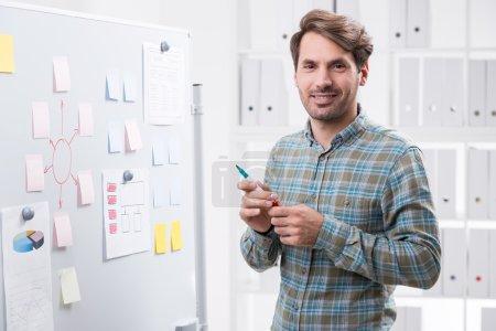 Photo pour Homme d'affaires souriant près du tableau blanc prêt pour la présentation du projet. Étagères avec des dossiers en arrière-plan. Concept de travail d'entreprise - image libre de droit