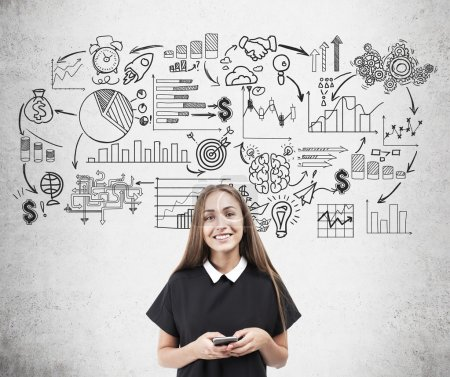 Photo pour Femme d'affaires souriante debout près croquis de démarrage noir et blanc sur le mur de béton. Concept de planification et de stratégie en entreprise - image libre de droit