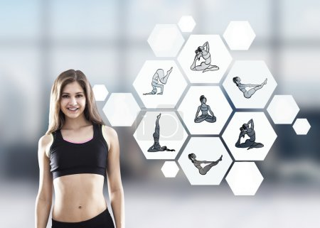 Smiling girl in gym with yoga sketches