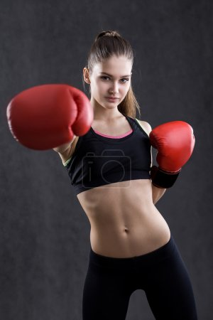 Girl in sportswear with boxing gloves